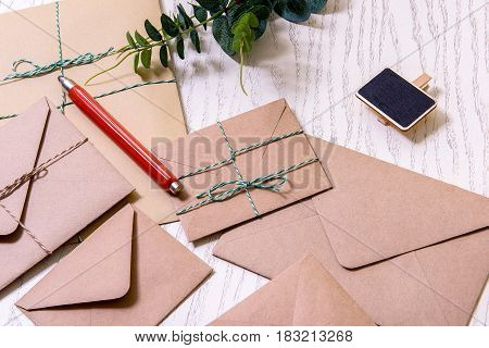Red pencil is on brown envelopes. Green plant near black pin
