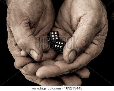 Dice, black in color, are in men's hands.