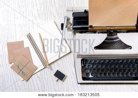 Vintage typewriter is beside unclosed drawing block and brow envelopes. Top view