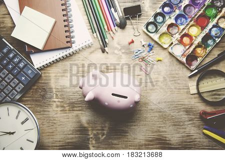 Pencil cup with crayons piggy bank on copybooks