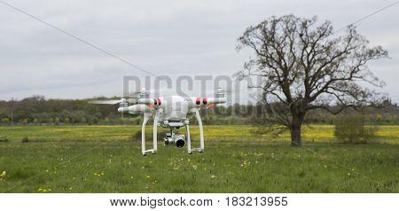 SWINDON UK - APRIL 21 2016: DJI Phantom Drone flys over farmland
