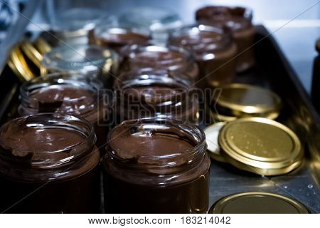 Chocolate spread in spoon with jar on dark background. The process of preparing bottling of nutella in cans
