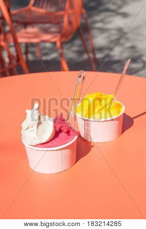 bright delicious ice cream in paper cups on orange table
