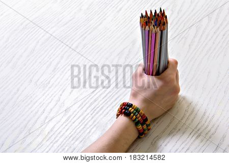 Close up of female hand clenching amount of crayons. Top view. Copy space