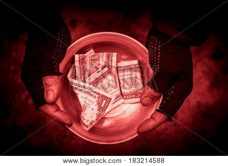 Dirty hands man clamped the metal bowl. In the bowl there is money.