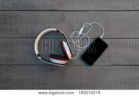 headphones and telephone on Wooden background . smartphone and headphones banner template with text place. Music listening or concept photo. Black screen phone top view.