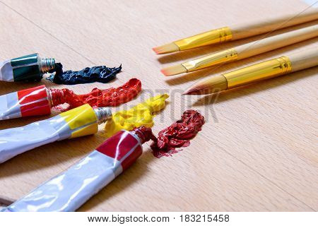 Professional tassels are in front of tubes with bright paint. Close up