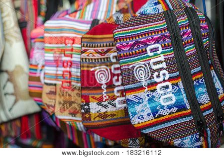 CUZCO PERU 08 FEBRUARY 2017: Colourful waist bags with sign Cusco at souvenir market