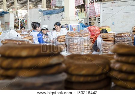 CUZCO PERU 08 FEBRUARY 2017: bread sellers at the market behing stalks of fresh bread