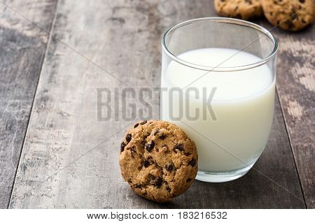 Chocolate chip cookies and milk on wooden table background