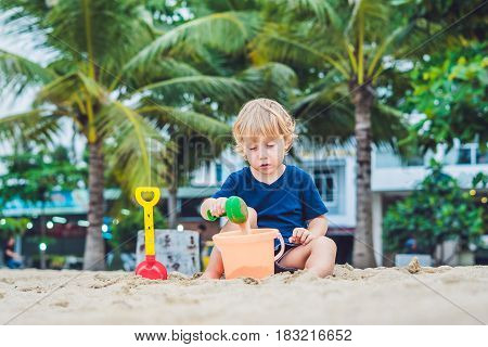 Kid Playing On The Beach With The Children's Shovel And A Bucket