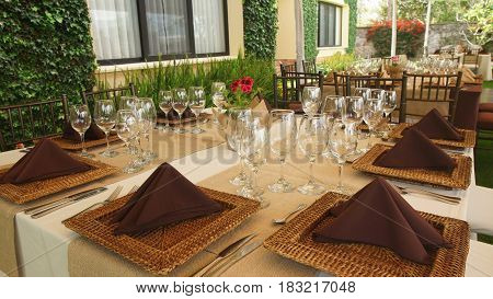 Tables decorated and arranged for a celebration lunch in the garden of a house in the morning