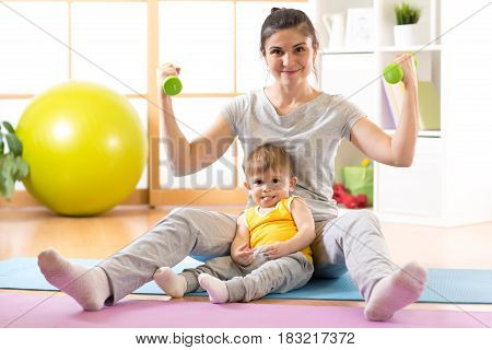 Sportive laughing mother with baby boy and dumbbells in hands. Motherhood is not a cause to let oneself go