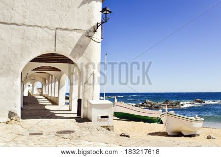 a view of the Port Bo Square in Calella de Palafrugell, Costa Brava, Catalonia, Spain, with its characteristics white houses with portico and some old fishing boat stranded on the Barques Beach