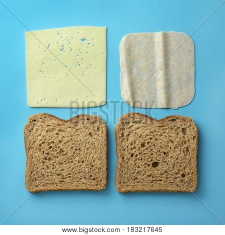 high-angle shot of the ingredients to prepare a ham and cheese sandwich, a pair of slices of brown bread, a slice of ham and a slice of cheese on a blue background