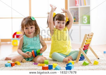 Little kids playing with abacus and constructor toys, early learning
