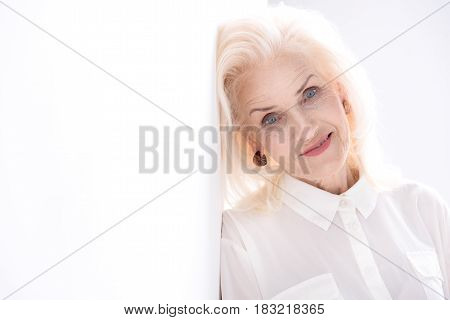 Lightly smiling old woman is inclining on wall and looking at camera with wisdom. Isolated. Copy space