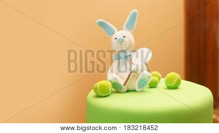 Rabbit with racket and tennis balls made of sugar on a cake with green sugar coating on a pastel colored background