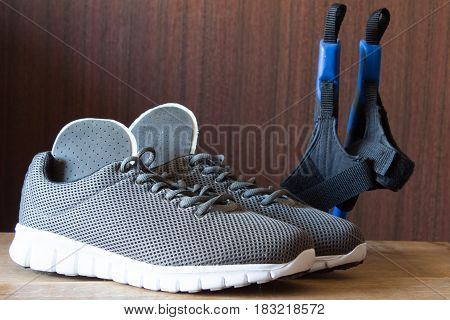 Gray sport shoes with Nordic Walking sticks and orthopedic insoles. Pair of sneakers on wooden background