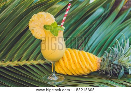 Pineapple And Pineapple Smoothies Against The Background Of A Branch Of A Palm Tree