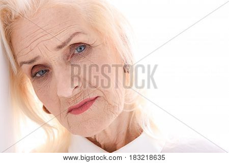Life experience is in eyes of mature sad woman. She looking at camera with wistfulness. Isolated. Copy space