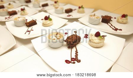 Three different decorated desserts served in white ceramic square plates on pastel colored background