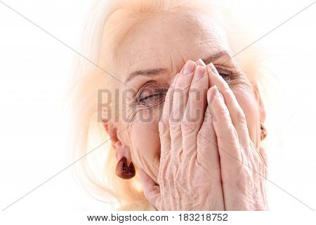 Funny joke. Happy old lady is in good mood. She closed her face by hands with laugh. Isolated