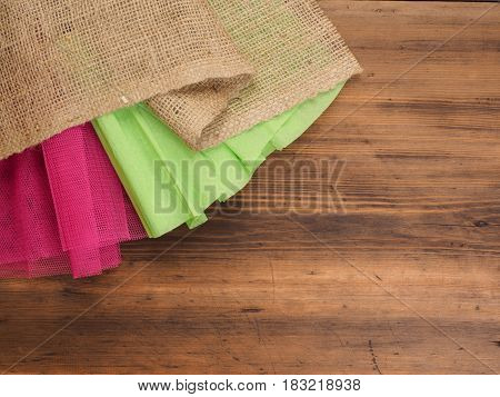 Creative, rustic background. The composition of burlap, crinkled green paper and a red grid on a brown background from old wood, rural table. Mock-up for your greetings card, poster or design