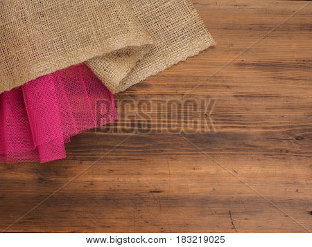 Creative, rustic background. The composition of burlap and a red grid on a brown background from old wood, rural table. Mock-up for your greetings card, poster or design