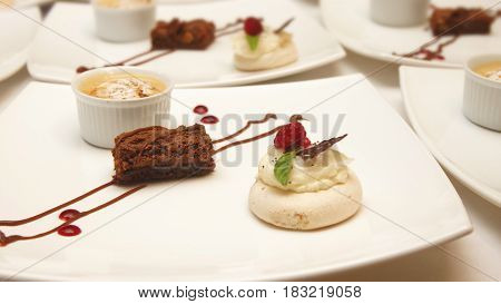 Three different decorated desserts served in white ceramic square plates on white table
