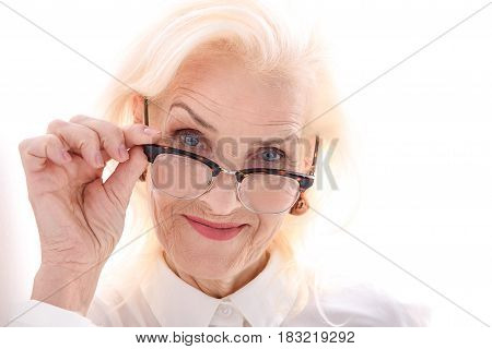Old lady in eyewear is holding glasses and looking at camera with bright smile. Isolated. Portrait