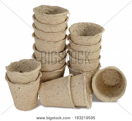 a bunch of pitchers cups of peat for seedlings of plants inserted into one another stand in a row and are on the table isolated on white background