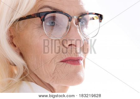 Confident mature lady in eyewear is looking aside with determination. Isolated. Copy space. Portrait