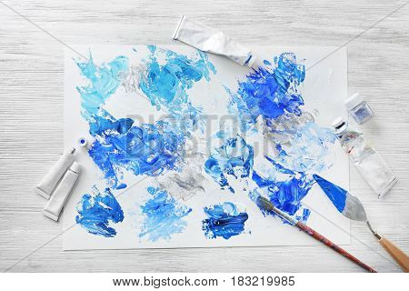 Painter's tools and paper with colorful abstraction on white wooden background