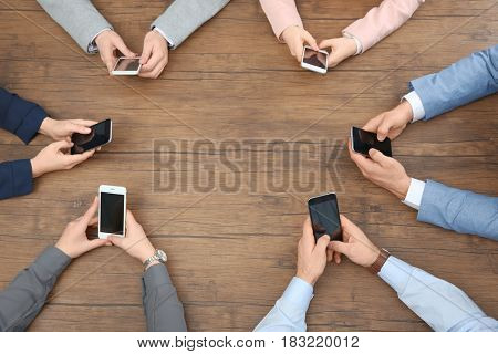 People sitting at table and using smartphones, top view