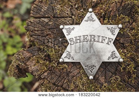 Sheriff badge on wooden background. Macro shot.