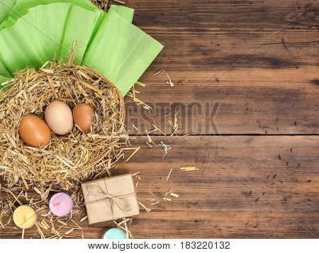 Brown eggs in hay nest. Rural eco background with brown chicken eggs, straw, gift box colored candles and paper on the background of old wooden planks. Top view. Background for Easter cards.