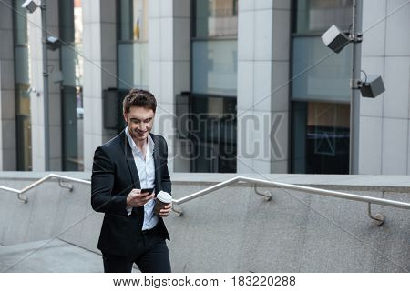 Busy man using phone and drinking coffee