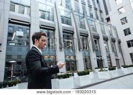 Busy young man working with smartphone in business center