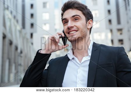 Portrait of smiling businessman talking on phone in the city