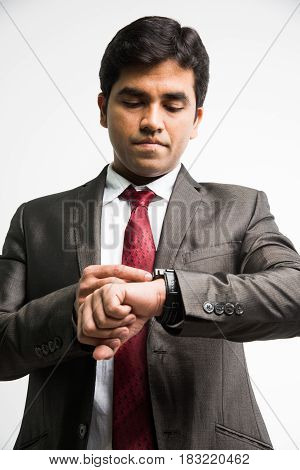 time is money concept - Indian young businessman looking / setting time in wristwatch, standing isolated over white background