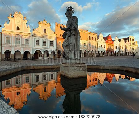 Evening view of Telc or Teltsch town square building mirroring in public fountain with statue of st. Margaret Czech republic. World heritage site by unesco