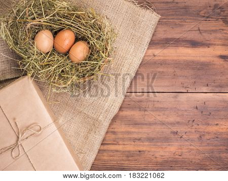 Rural eco background with brown chicken eggs, gift box and straw on the background of old wooden planks. The view from the top. Creative background for Easter cards, menu or advertising