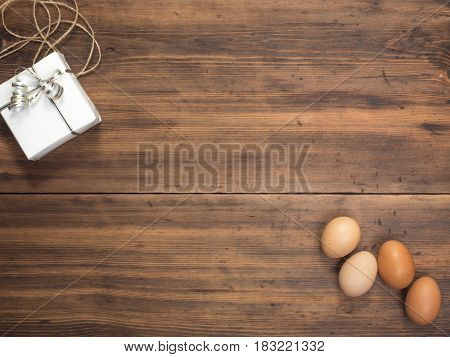 Easter eggs, gift box on old wooden table from planks. Top view with space for your design, Easter greetings or advertising. Rustic background. Composition of eggs and gift boxes tied with string
