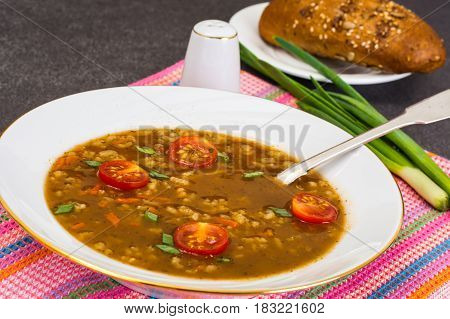 Spicy soup with curry, rice and grilled tomatoes. Studio Photo