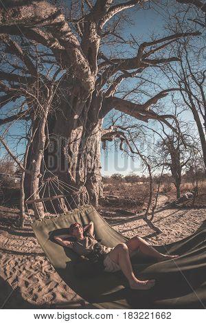 Couple Taking Selfie On Hammock Hanging From Huge Baobab Tree In The African Savannah. Fisheye View,