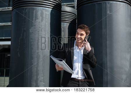 Young busy man looking away while talking on phone outdoors