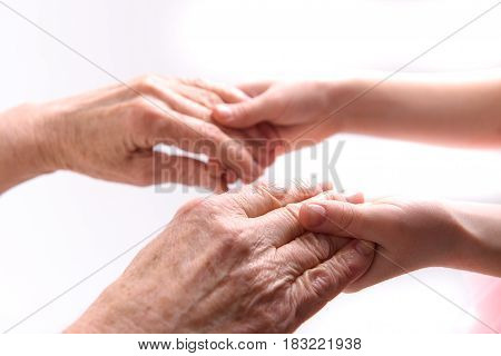 Hands of old lady are in small palms of child. Close up. Isolated
