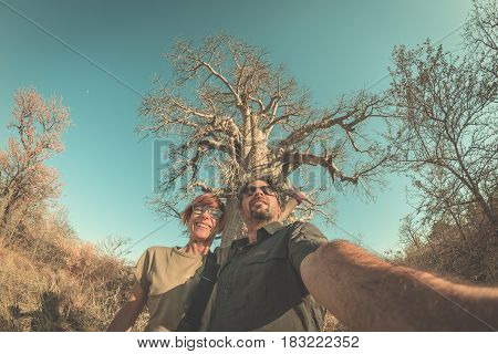 Couple Taking Selfie Near Baobab Plant In The African Savannah With Clear Blue Sky. Fisheye View Fro