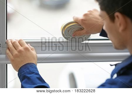 Young worker applying rubber strip onto window in office